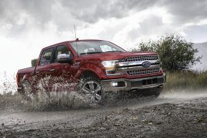 2020 ford f-150 lariat in red driving through mud