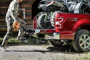 man in tree camo loading an atv into a red 2020 ford f-150 xlt
